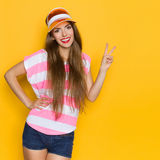 Summer Girl In Sun Visor Showing Peace Sign. Smiling young woman in pink stripped shirt, jeans shorts and orange sun visor posing with hand on hip and showing Royalty Free Stock Photos
