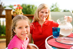 Summer: Girl at Table with Mother Behind Royalty Free Stock Photography