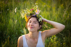 Summer. Girl with wreath on the head looking up in summer evening stock image