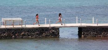 Summer girls running across bridge swimsuit Stock Photo