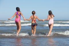 Summer girls. Three happy girls running into the ocean stock photo