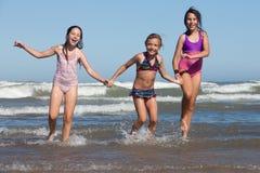 Summer girls. Three happy girls running out of ocean stock photos