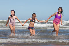 Summer girls. Three happy girls running out of ocean royalty free stock images