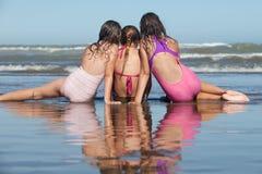 Summer girls. Three girls sitting on the beach stock images