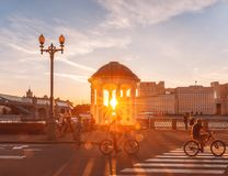 Summer in Gorky Park. Sun rays on the road with a bicyclist. stock photos