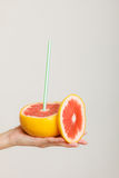 Summer. Grapefruit with drinking straw in hand Royalty Free Stock Image