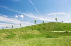 Summer green field and hills over blue sky Stock Images