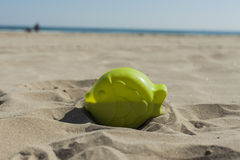 Summer green fish beach toy affix in the dry sand. Selective foc Stock Photography
