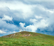 Summer green mountain top and cloudy sky. Green grass covered summer mountain top and overcast cloudy sky Stock Images