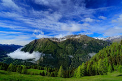 Summer green mountains with blue sky and white clouds. Mountains in the Alps. Mountain scenery in summer. Green meadow with mounta Royalty Free Stock Images