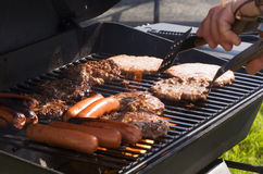 Summer Grilling. Hotdogs and hamburgers on the grill at a summer cookout Stock Image