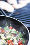 Summer grilling. Vegetables saute as the chicken hits the grill. Summer time and grilling season is here Stock Photos