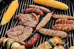 Summer grilling. Grilling: corn, sausages, shish kebab, shoulder and chicken. Typical grill food Royalty Free Stock Images