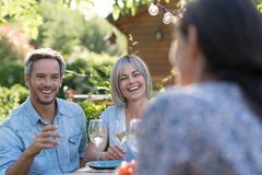 Summer. Group of friends gathered around a table in the garden. In summer. Group of friends gathered around a table in the garden to share a meal. Three people Royalty Free Stock Images