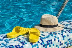 Straw hat and yellow flip-flops by the pool at the seaside resort. Summer ha yellow flip-flops by the pool at the seaside resort royalty free stock photos