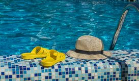 Straw hat and yellow flip-flops by the pool at the seaside resort. Summer ha yellow flip-flops by the pool at the seaside resort stock photo
