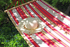 Summer: hammock with a lady`s sunhat. Hanging in a garden Stock Photography