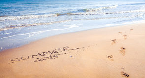 Summer 2015 handwriting and footprints in the sand. Royalty Free Stock Image