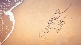 Summer 2015 handwriting on the sand. Stock Photo