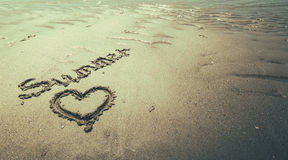 Summer handwritten in the sand of the beach with a lovely heart stock photography