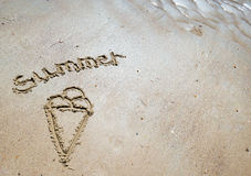 Summer handwritten in the sand of the beach with a lovely heart stock image