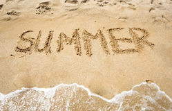 Summer handwritten on wet sand at seashore Stock Photos