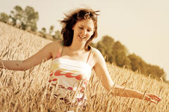 Summer happiness. Young girl enjoy at sunny day on the wheat field Stock Photography