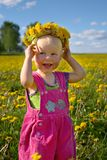 Summer happiness. Little smiling girl with dandelion wreath Royalty Free Stock Image