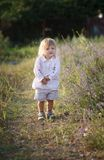 Summer harmony. A blond-haired girl walking on a grassy track along a seaside towards a green hill, backshot Royalty Free Stock Images