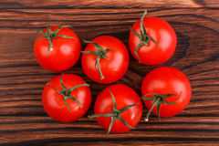 Summer harvest of bright red tomatoes with leaves on a dark brown wooden background. Juicy, ripe and fresh tomatoes. Vegetables. Stock Photography