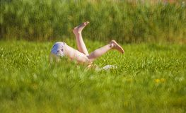 Summer has come!. A girl tumbling in the grass on a summer meadow stock photography