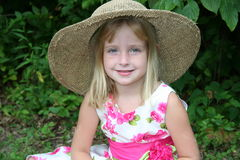 Summer hat. Young girl sitting in the shade wearing a big hat Stock Photo