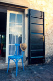Summer hat on blue chair in front of entrance in Prove. Summer straw hat on blue chair, in front of entrance in a beautiful Provence house in setting sunlight Royalty Free Stock Photo