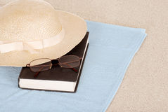 Summer hat book and glasses on the beach Stock Images