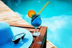Summer hat, a cocktail and sunglasses near the luxurious pool. Royalty Free Stock Images