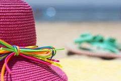 Summer hat and flip flops on a beach Royalty Free Stock Photo
