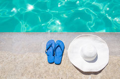 Summer hat and flip flops near the pool Royalty Free Stock Photography