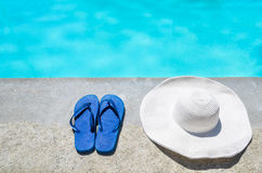Summer hat and flip flops near the pool Stock Photos