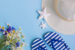 Summer hat, flowers and flip flops on a blue background. Top view, flat lay stock photography
