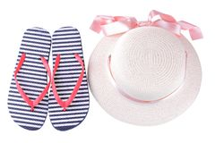 Hat with a pink ribbon and flip flops in blue and white stripes. Isolated. Summer hat with a pink ribbon and flip flops in blue and white stripes. Isolated stock images