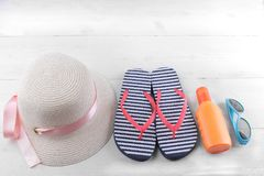 hat with a pink ribbon, Vietnamese, suntan cream and blue sunglasses. White wooden background. royalty free stock images