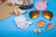 Summer hat, sea shells, sunglasses and  ship on blue background Royalty Free Stock Images