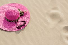 Summer hat and sunglasses on sand Royalty Free Stock Image