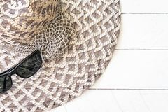 Summer hat with  sunglasses on white wooden. Background Royalty Free Stock Image