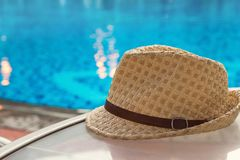Summer hat on table near bright blue pool, copy space, selective focus. Vacation and summer holidays concept.  royalty free stock images