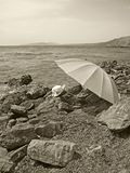 Summer hat and umbrella on a stony beach Stock Photography