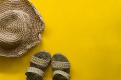 Summer hat weave and sandal weave with yellow background royalty free stock image