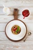 Summer healthy breakfast of granola, muesli with milk jug with red currant decor on light wooden board. Stock Photo