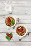 Summer healthy breakfast for two person of granola, muesli with milk jug with red currant decor on light wooden board. Stock Images