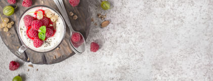 Summer healthy dessert with raspberries and yogurt on the cutting board. Banner format Stock Images